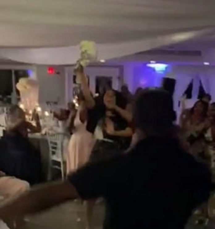 Guest steal bride's bouquet from a woman who caught it during the bouquet toss